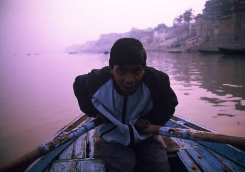 ガンジス河で舟をこいでいる少年