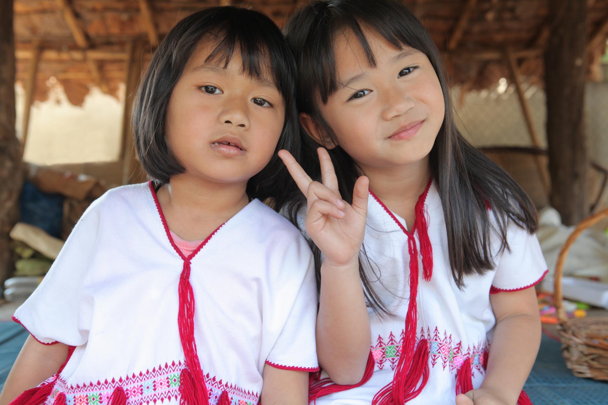 純潔、未婚を表す白の民族衣装を着たカレン族の幼い姉妹