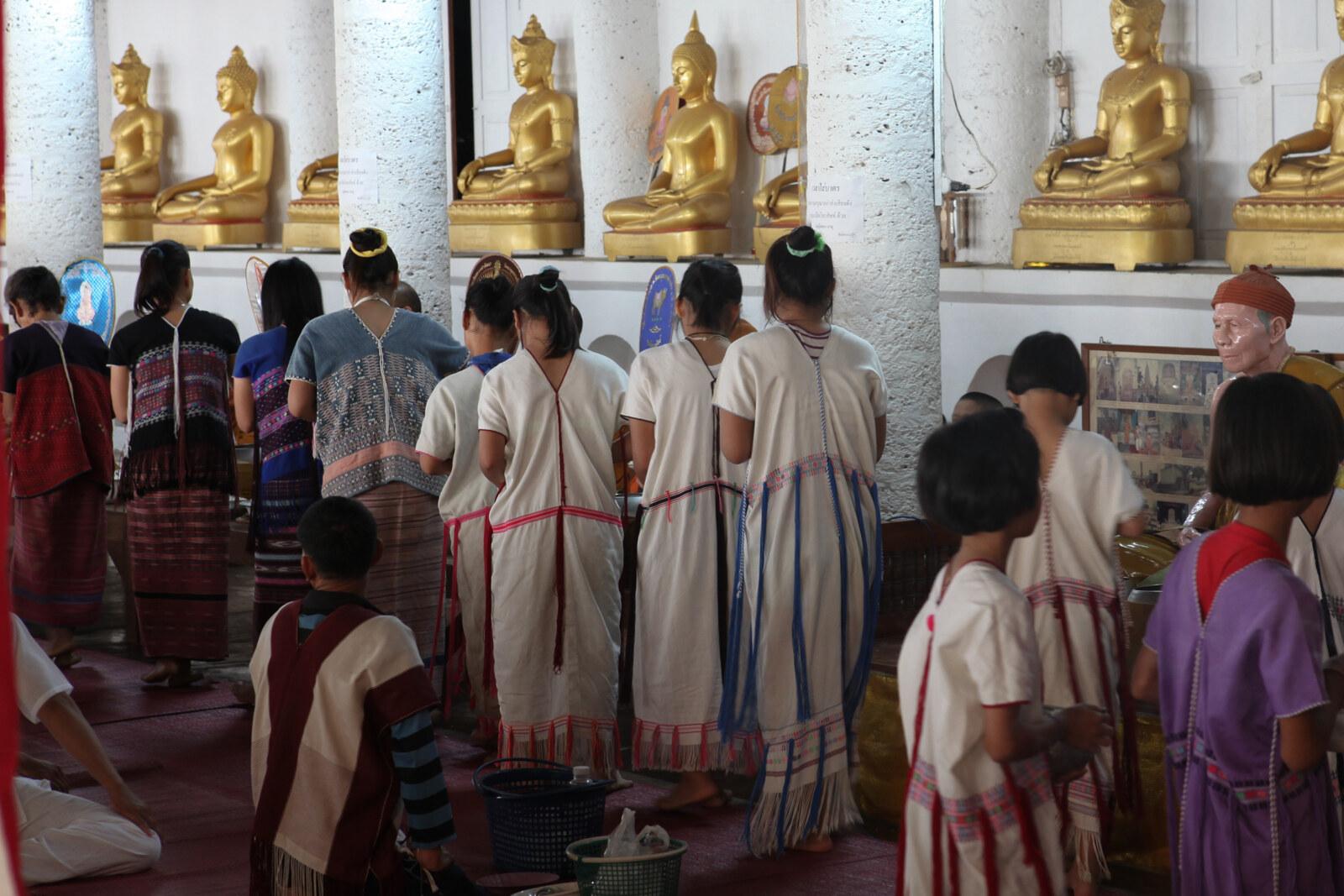 早朝のタンブン(徳を積むこと) - 敬虔な仏教徒であるカレン族は、早朝、境内で僧に食事を供える。